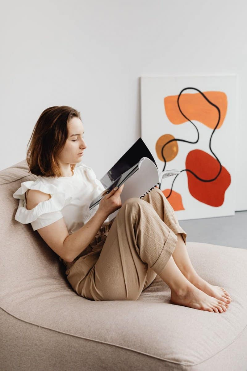 a woman reading a book while in a chair