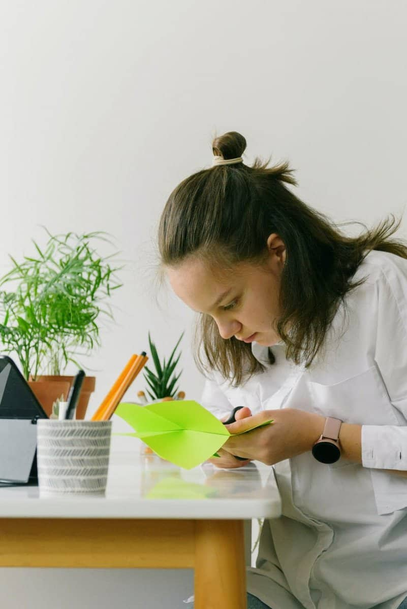 a teenager making a papercraft project at home